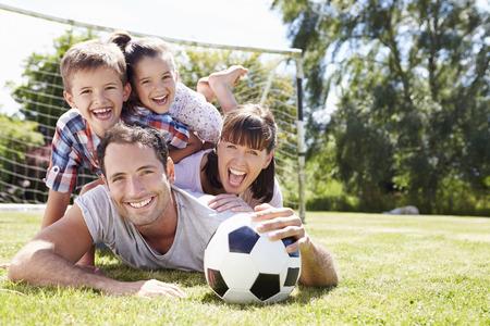 people together: Familia que juega al balompi� en jard�n junto Foto de archivo