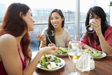 mujeres juntas: Tres amigos femeninos que disfruta del almuerzo en restaurante en la azotea Foto de archivo