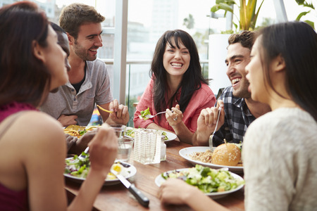 hispanic: Group Of Friends Enjoying Meal At Rooftop Restaurant