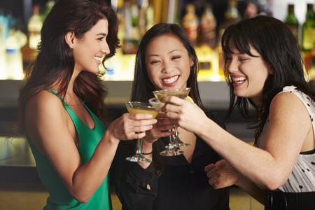amigos hablando: Tres amigos femeninos que disfrutan de la bebida En Cocktail Bar Foto de archivo