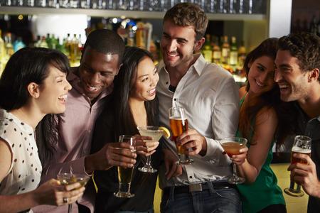 hombre tomando cerveza: Grupo de amigos que disfrutan de la bebida en bar