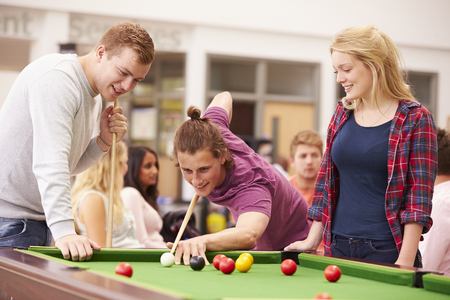 19 years old: College Students Relaxing And Playing Pool Together Stock Photo