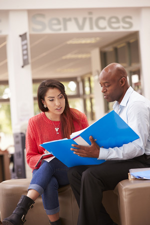 college: College Student Having Meeting With Tutor To Discuss Work Stock Photo