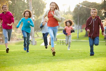 gente corriendo: Grupo de niños jovenes corriendo hacia la cámara en el parque Foto de archivo