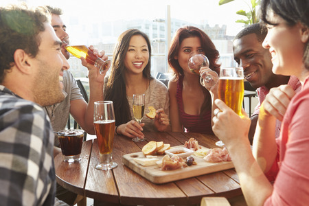 friend: Group Of Friends Enjoying Drink And Snack In Rooftop Bar