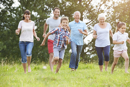 familia feliz: Multi generacional corriendo por el campo juntos