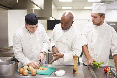 cocinero: Ayuda del profesor de formación los estudiantes a trabajar en la restauración Foto de archivo
