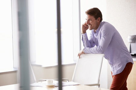 casually dressed: Casually Dressed Businessman Using Mobile Phone In Office Stock Photo
