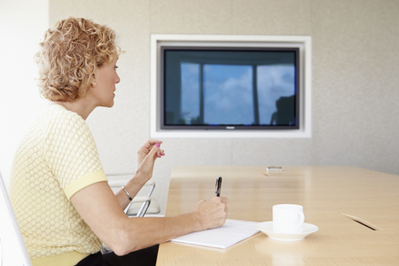 video conference: Senior Businesswoman Having Video Conference In Boardroom