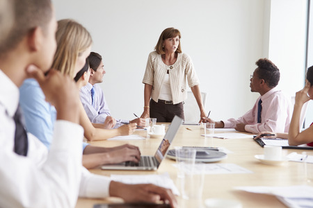 chairman: Group Of Businesspeople Meeting Around Boardroom Table Stock Photo
