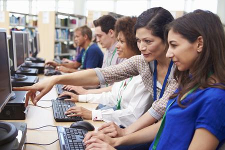 education: Grupa dojrzałych studentów pracujących w komputerach z Tutor