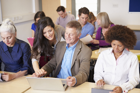 further: Mature Students In Further Education Class With Teacher