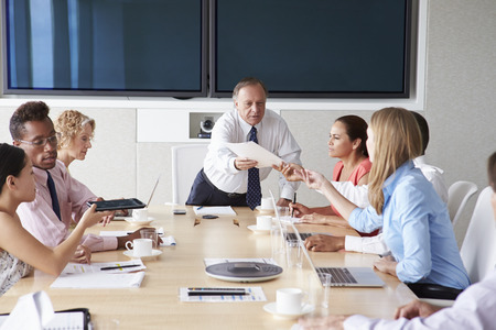 work group: Group Of Businesspeople Meeting Around Boardroom Table Stock Photo