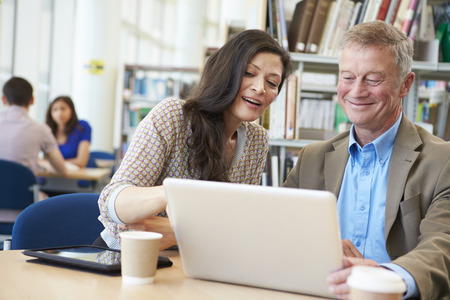 Enseignant Aider Étudiant d'âge mûr avec des études en bibliothèque