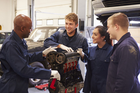 mechanics: Teacher Helping Students Training To Be Car Mechanics