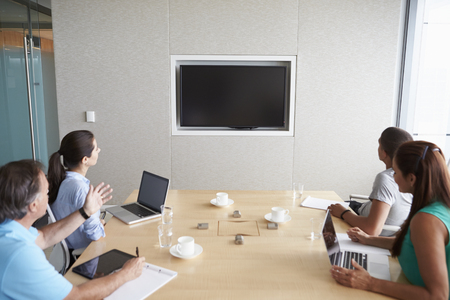 video conference: Four Businesspeople Having Video Conference In Boardroom
