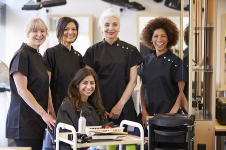 Teacher Helping Mature Students In Hairdressing Stockfoto