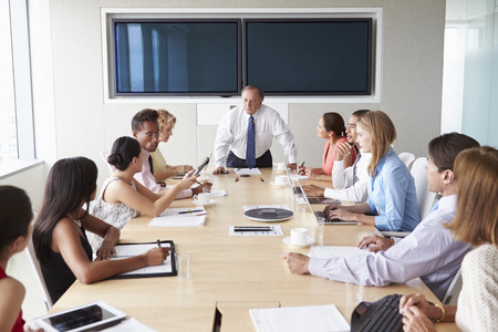 Group Of Businesspeople Meeting Around Boardroom Table Фото со стока