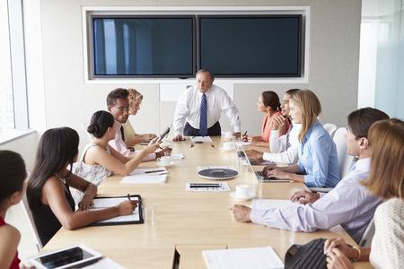 Group Of Businesspeople Meeting Around Boardroom Table Stock fotó
