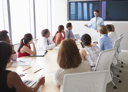 group cooperation: Group Of Businesspeople Meeting Around Boardroom Table Stock Photo