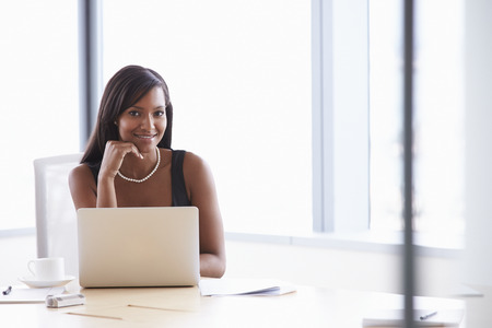 african american woman smiling: Businesswoman Working On Laptop At Boardroom Table