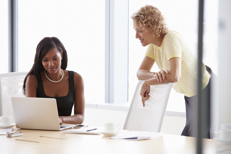 Two Businesswomen Working Together On Laptop In Boardroom