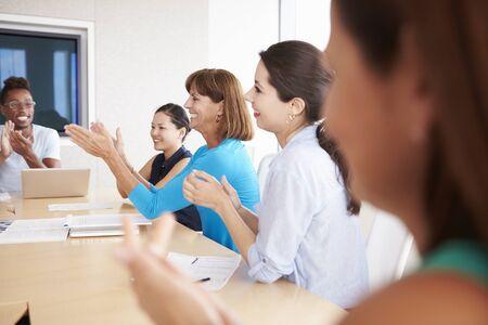 applauding: Businesspeople Applauding Colleague In Boardroom