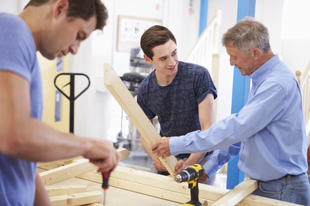 assisting: Teacher Helping College Student Studying Carpentry