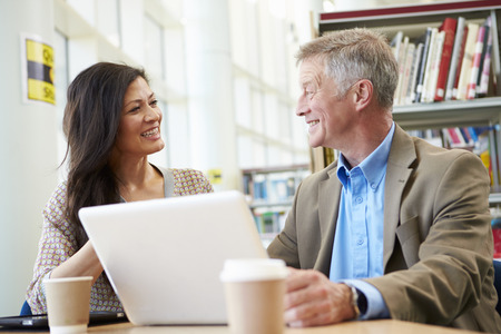 the elderly tutor: Teacher Helping Mature Student With Studies In Library