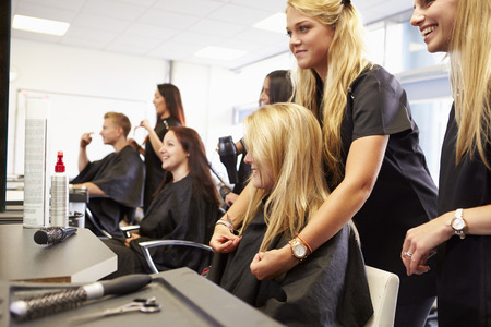 salon: Teacher Helping Students Training To Become Hairdressers