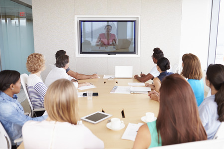 meeting table: Group Of Businesspeople Having Video Conference In Boardroom
