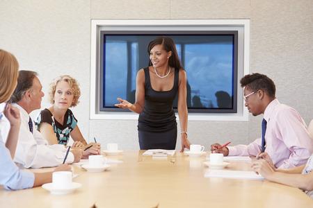 mujer sentada: Empresaria Por Pantalla Abordar Sala de reuniones