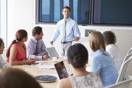 speaker: Motivational Speaker Talking To Businesspeople In Boardroom Stock Photo