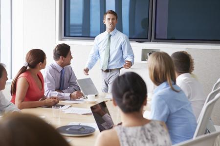 PARLANTE: Orador motivacional que habla con empresarios en la sala de reunión Foto de archivo