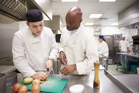 chefs: Teacher Helping Students Training To Work In Catering