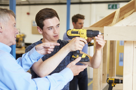 student studying: Teacher Helping College Student Studying Carpentry