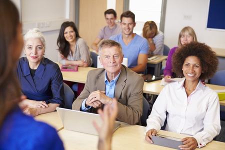 Starší studenti v dalším vzdělávání třídě s učitelem Reklamní fotografie