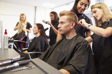 peluqueria: Ayuda del profesor de formación los estudiantes a convertirse Peluquerías Foto de archivo