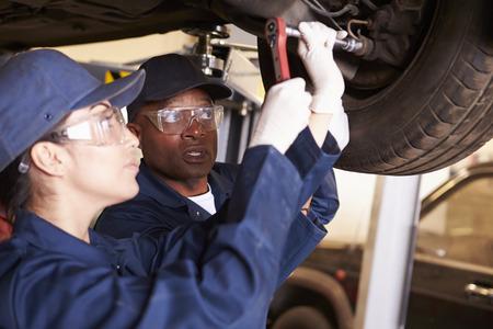 ENTRENANDO: Ayuda del profesor de Formación estudiante sea mecánicos de coche Foto de archivo