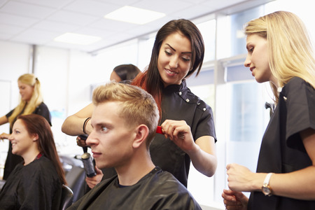 hairdresser salon: Teacher Helping Students Training To Become Hairdressers