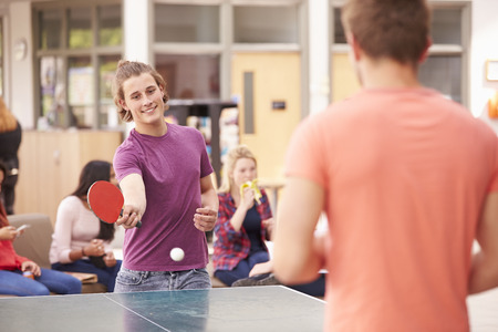 teens playing: College Students Relaxing And Playing Table Tennis