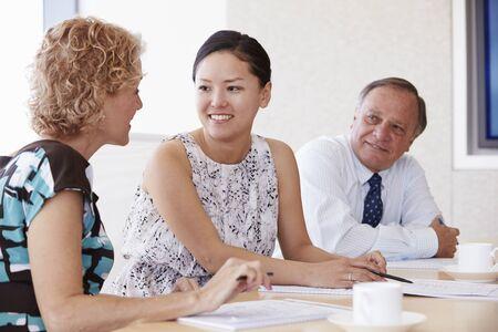 senior women: Three Businesspeople Having Meeting In Boardroom