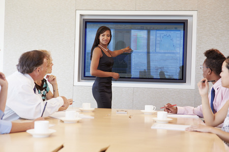 african business man: Businesswoman By Screen Addressing Boardroom Meeting