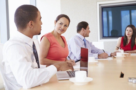 work table: Four Hispanic Businesspeople Having Meeting In Boardroom