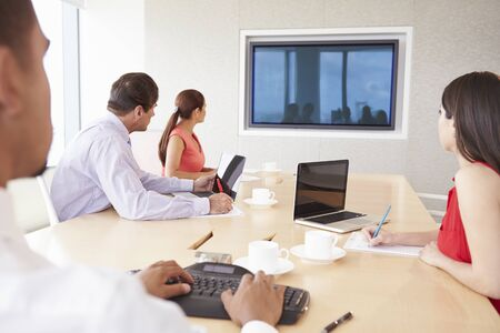 video screen: Four Businesspeople Having Video Conference In Boardroom