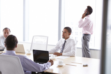 mobile telephone: Four Businessmen Having Meeting Around Boardroom Table