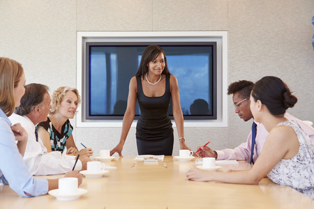 boardroom: Businesswoman By Screen Addressing Boardroom Meeting