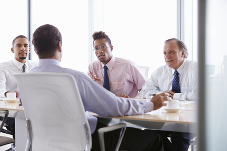 sitting at desk: Four Businessmen Having Meeting Around Boardroom Table