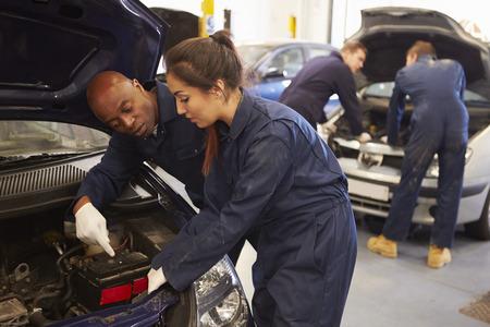two car garage: Teacher Helping Student Training To Be Car Mechanics
