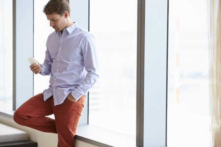 one person: Casually Dressed Businessman Using Mobile Phone In Office Stock Photo